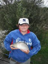Mark Glew aged 13yrs with a common carp weighing 2lb again caught on bread flake floated on top.