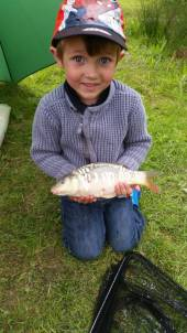 Harrison with his lovely little mirror carp.